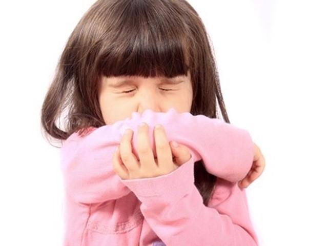 Kind niest met arm voor de mond