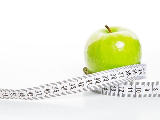 Groene appel met een meetlint er omheen