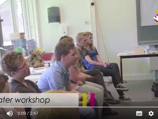 Still uit een video van de theaterworkshop waar jongeren op een rij zitten te luisteren