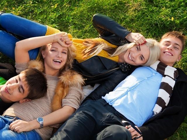 Vier jongeren liggend in het gras