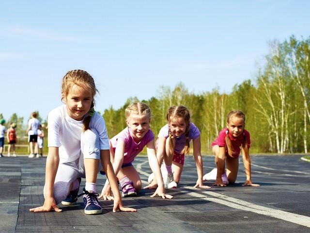 Vier kinderen op een rijtje van links naar rechts in start houding om te gaan hardlopen