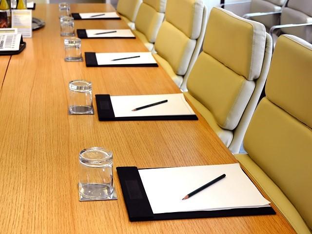 Overlegtafel met voor elke stoel papieren, een potlood en een omgedraaid glas