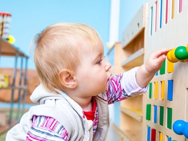 Baby speelt met speelgoed muur