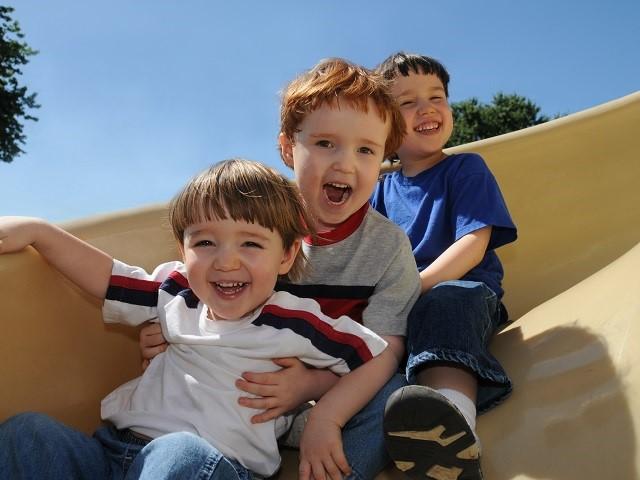 Drie kinderen in een treintje van de glijbaan