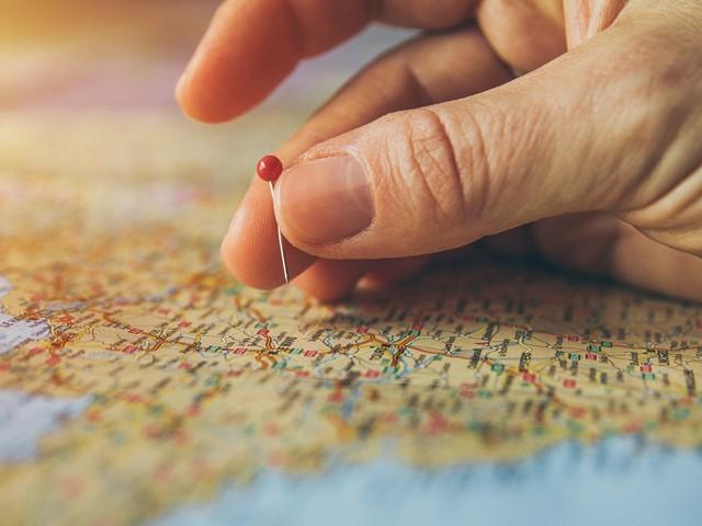 Hand markeert plaats op landkaart