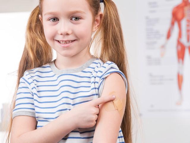 Meisje met pleister na vaccinatie