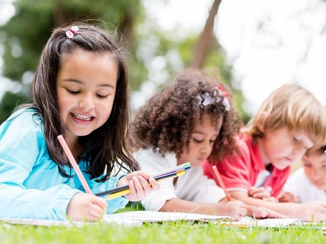 Vier kinderen aan het leren met boeken in het gras (1)