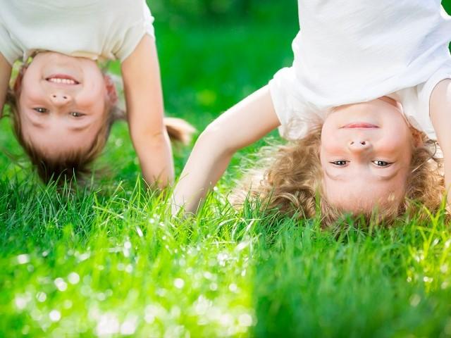 Close up van twee kinderen die op de kop staan in het gras