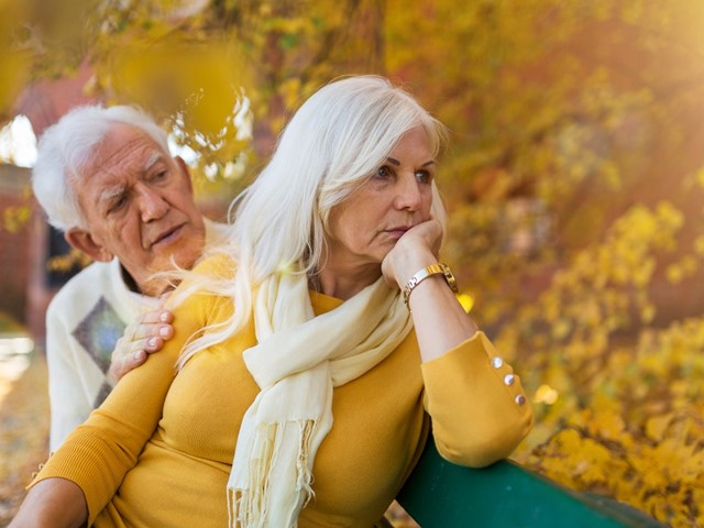 Twee oudere mensen op een bankje, waarbij de vrouw wegkijkt