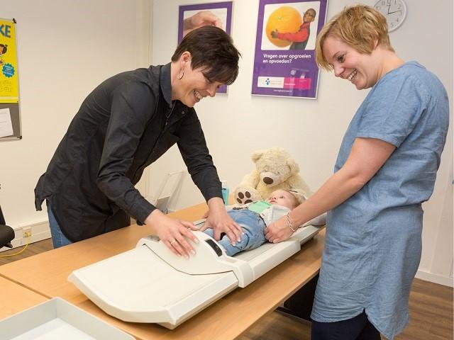 Kindje wordt door specialist gewogen en gemeten op consultatiebureau