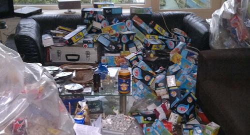 Woonkamer met daarin een berg aan afval en troep zoals plastic zakken en lege drinkpakken en vuile vaat
