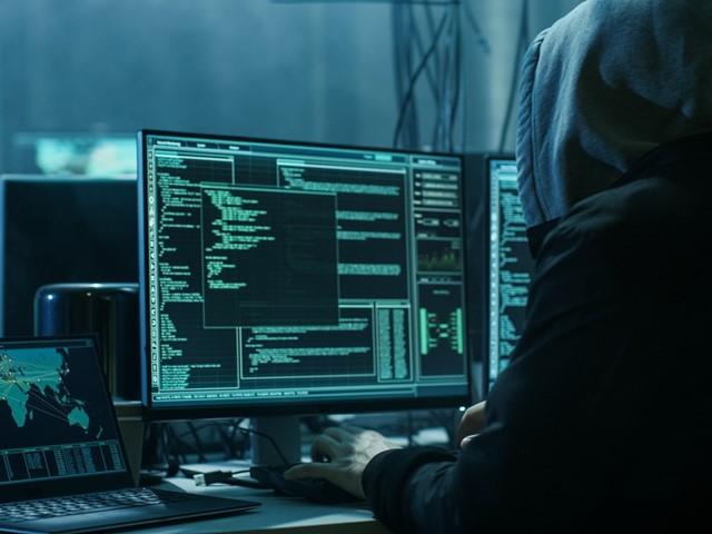 Iemand in een vest met capuchon die aan het coderen is, donkere foto