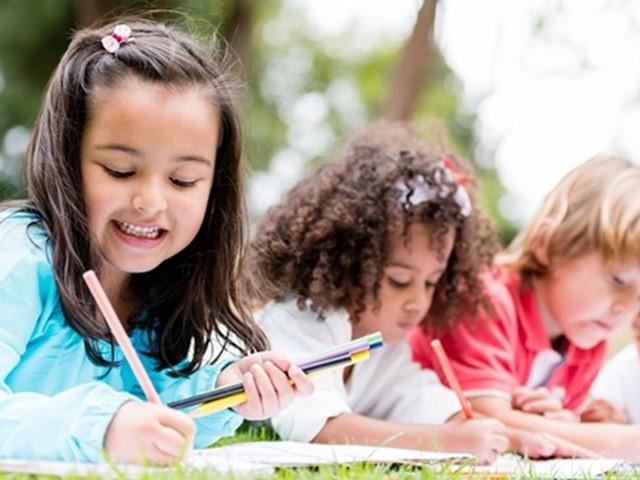 Vier kinderen aan het leren met boeken in het gras
