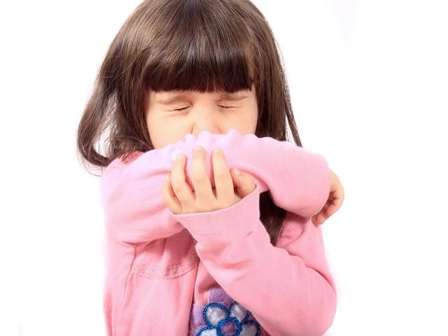 Kind niest in haar elleboog