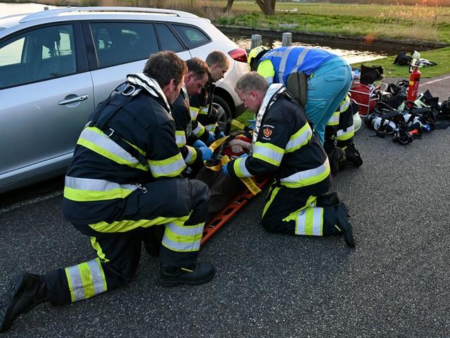 Meerdere brandweerleden en ambulancepersoneel helpen persoon op brancard