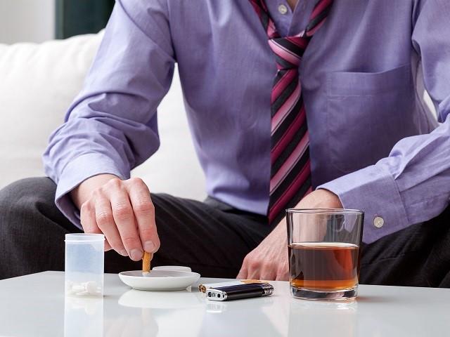 Man in pak zittend aan tafel met een glas alcohol, sigaretten en pillen