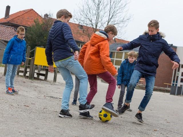 Vijf kinderen aan het voetballen op het schoolplein