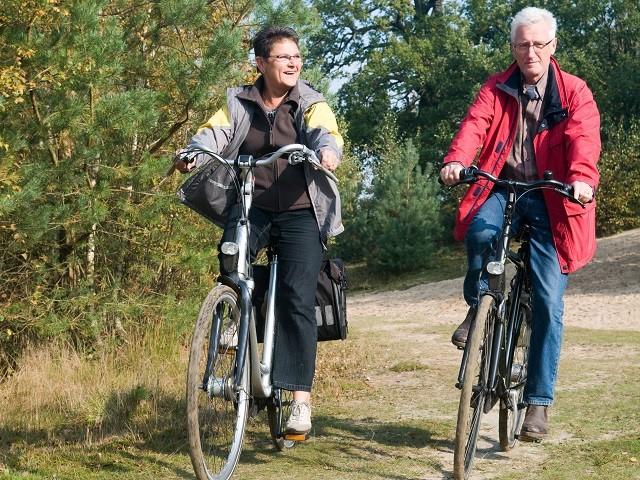 Twee volwassen mensen op de fiets in het bos